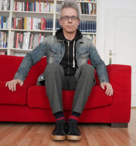 Thorsten Kacsich on a red couch and bookshelf in the background. He wears the black leather sneakers and a denim jacket.